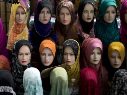 This picture taken on November 30, 2012 shows mannequins with the latest styles of headscarfs or 'hijab' on display outside a shop in downtown Kuala Lumpur. A Malaysian 'hijab', also called a tundung, is a head covering or scarf a woman can wear in public as a symbol of her …