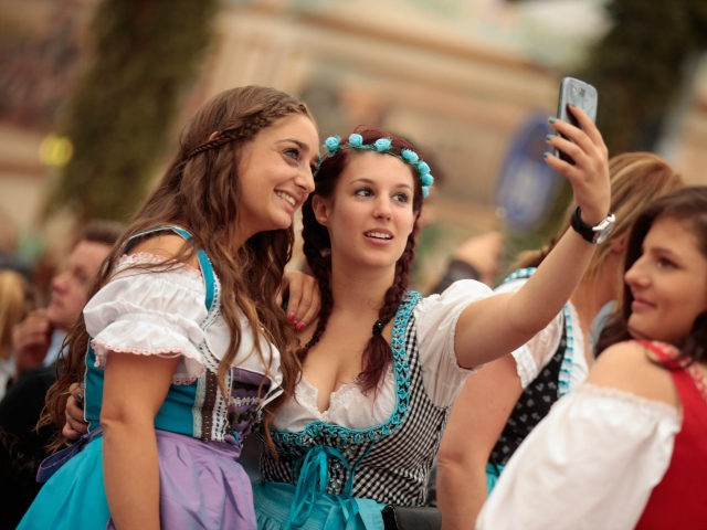 MUNICH, GERMANY - SEPTEMBER 19: Revelers dressed in Bavarian folk outfits pose for selfies during the opening day of the 2015 Oktoberfest on September 19, 2015 in Munich, Germany. The 182nd Oktoberfest will be open to the public from September 19 through October 4and will draw millions of visitors from …
