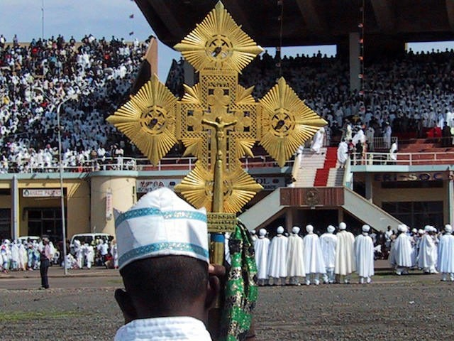 ASMARA, ERITREA: An Orthodox priest holds a cross during the Meskel festival, the biggest Orthodox ceremony, 27 September 2004 in Asmara in Eritrea. Thousands of people gather each year in the Eritrean capital to celebrate the finding of Christ's cross by Saint Helen, some 1700 years ago. AFP PHOTO NICOLAS …