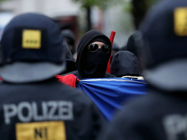 BERLIN, GERMANY - MAY 01: A leftist demonstrator faces riot police during the 'Revolutionary 1st of May' May Day protest in Kreuzberg district on May 1, 2017 in Berlin, Germany. Labour unions and leftists each had their own marches across the city today and thousands of revelers celebrated at the …