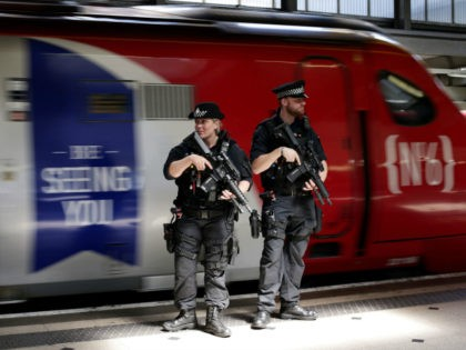 TOPSHOT - Armed British Transport Police Specialist Operations officers patrol on the platform before boarding a Virgin train to Birmingham New Street, at Euston station in London. For the first time, asof May 25, 2017, specially trained firearms officers will be patrolling on board trains as part of threat level …