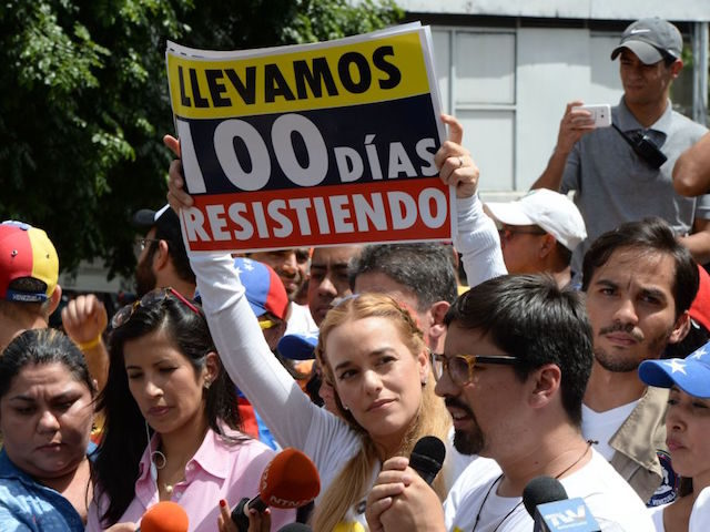 "Lilian Tintori, wife of Venezuelan political prisoner and opposition leader Leopoldo Lopez, holds a placard reading ""We Have Been Resisting For 100 Days"" as the vice-president of the National Assembly, Freddy Guevara delivers a speech during a demonstration marking 100 days of protests against President Nicolas Maduro in Caracas, on …"