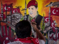 ISTANBUL, TURKEY - JULY 12: A man puts the finishing touches on a painting depicting the events of the July 15, 2016 coup attempt at an anniversary site setup to mark the first anniversary of the failed coup attempt in Taksim square on July 12, 2017 in Istanbul, Turkey. July …