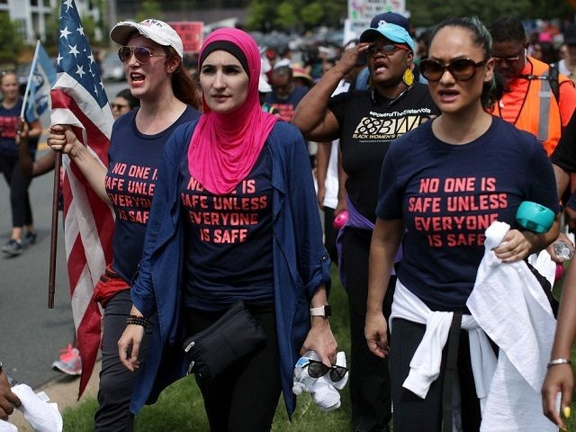 Activist Linda Sarsour (C) and fellow gun-control activists participate in a march beginning at the headquarters of National Rifle Association July 14, 2017 in Fairfax, Virginia. Women's March holds a two-day rally and march from the NRA headquarters to the Justice Department in Washington, DC, to protest the association's 'incendiary …