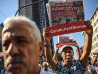"Journalists hold banners reading ""Cumhuriyet won't be silenced"" and copies of Cumhuriyet opposition daily reading ""We want Justice"" as they march to the courthouse from Cumhuriyet daily's headquarters on July 24, 2017 in Istanbul. Seventeen directors and journalists from one of Turkey's most respected opposition newspapers go on trial on …"