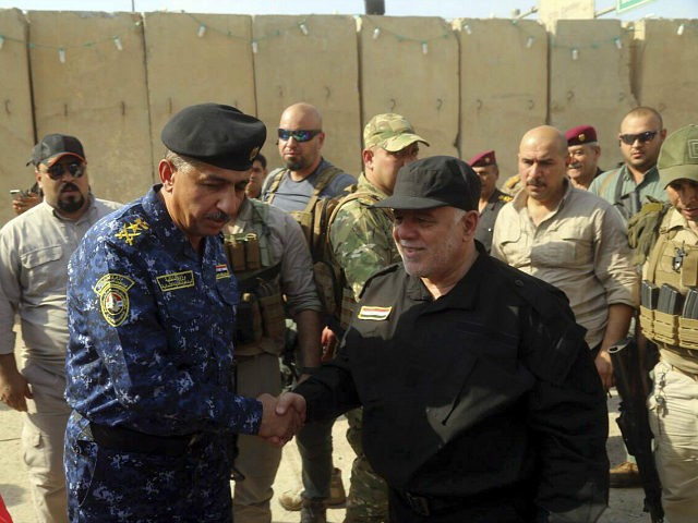 Iraq's Prime Minister Haider al-Abadi, center right, shakes hands with Lieutenant General Raid Shaker Jawlat, center left, the commander of Iraqi federal police upon his arrival in Mosul, Iraq, Sunday, July 9, 2017. Backed by the U.S.-led coalition, Iraq launched the operation to retake Mosul from Islamic State militants in …