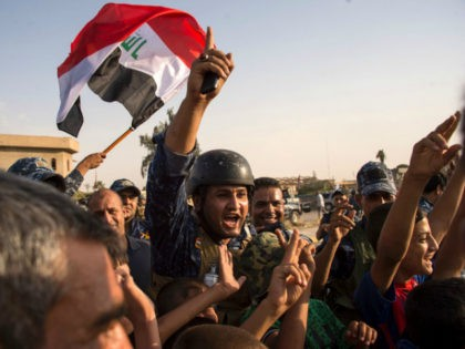 Members of Iraq's federal police force wave Iraq's national flag as they celebrate in the Old City of Mosul on July 9, 2017 after recapturing the city. Photo: AFP /Fadel Senna