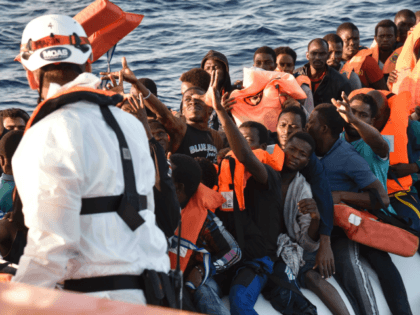Migrants and refugees seated on a rubber boat grab life jackets thrown by members of the crew of the Topaz Responder rescue ship run by Maltese NGO Moas and Italian Red Cross, off the Libyan coast in the Mediterranean Sea, on November 3, 2016.