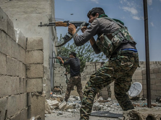 Fighters of the People's Protection Units (YPG), a mainly-Kurdish militia in Syria, fires their guns towards positions of militants of the so called Islamic State (IS) in Al Sinaa neighborhood, eastern Raqqa, Syria, 06 July 2017. Syrian activists say Islamic State group fighters are battling to repel the advance of …