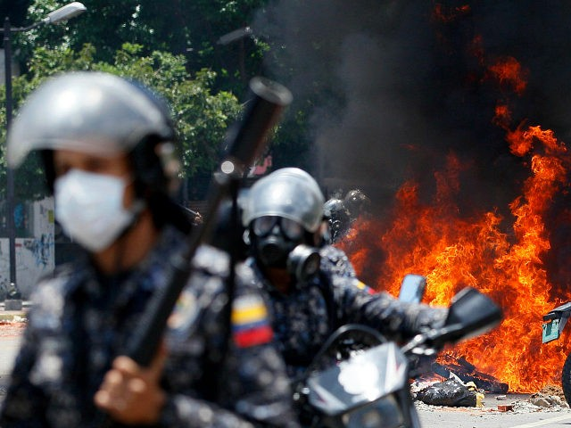 Venezuelan Bolivarian National police move away from the flames after an explosion at Altamira square during clashes against anti-government demonstrators in Caracas, Venezuela, Sunday, July 30, 2017. The explosion injured several officers and damaged several of their motorcycles. The officers were then seen throwing several privately owned motorcycles into the …