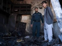 An Afghan policeman and a local resident inspect a burnt shop at the site of a car bomb attack in western Kabul on July 24, 2017. At least 24 people have been killed and 42 wounded after a car bomb struck a bus carrying government employees in western Kabul on July 24, an official told AFP, the latest attack to strike the Afghan capital. / AFP PHOTO / WAKIL KOHSAR (Photo credit should read WAKIL KOHSAR/AFP/Getty Images)