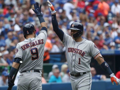 Carlos Correa of the Houston Astros is congratulated by Marwin Gonzalez after hitting a solo home run in the second inning during MLB game action against the Toronto Blue Jays July 9, 2017