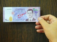 In this photo released by the Syrian official news agency SANA, a man displays a new bank note of 2,000 Syrian Lira, ($3.9), during a press conference for the Central Bank Governor Duraid Durgham in Damascus, Syria, Sunday, July 2, 2017. The notes are the first time the face of President Bashar Assad appears on the Syrian currency since he took office 17 years ago. (SANA via AP)