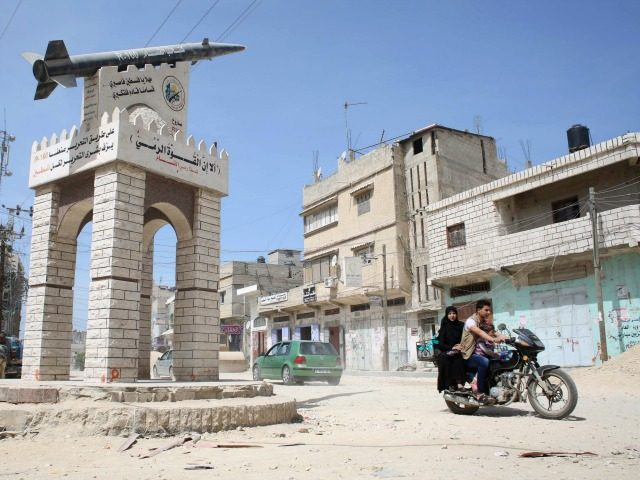 A Palestinian family ride a motorcycle past a model of a Gaza Strip made R-160 rocket, which is a new installation by militants of the Ezzedine al-Qassam Brigades, Hamas's armed wing, in the village of Khuzaa, east of Khan Yunis, in the southern Gaza Strip on March 26, 2015. AFP …