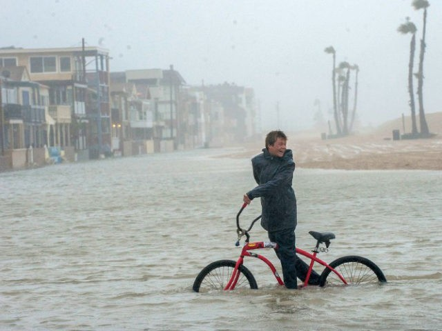 Jake Hart, 13, plays in the rising floodwater during a storm in Seal Beach, Calif., Sunday, Jan. 22, 2017. The heavy downpour on Sunday drenched Orange County in one of the heaviest storms of the year. Fast-moving floodwaters swept through California mountain communities and residents fled homes below hillsides scarred by wildfires as the third in the latest series of storms brought a deluge Sunday and warnings about damaging mudslides. (Ana Venegas/The Orange County Register via AP)