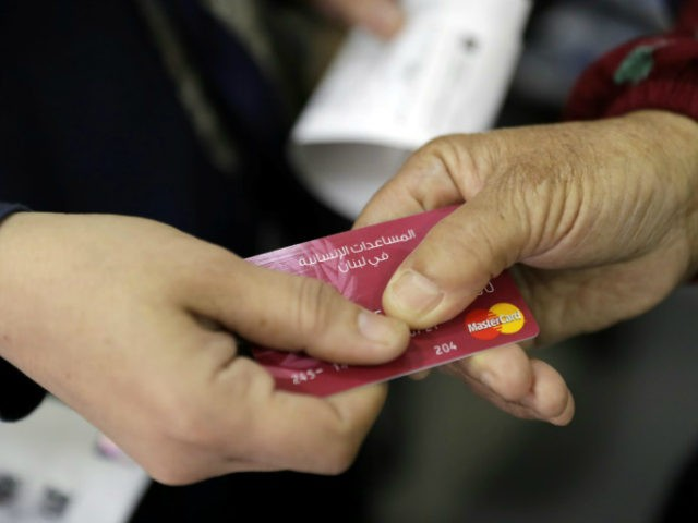 A Syrian refugee presents a World Food Programme debit card to a cashier in a Beirut shop on June 14, 2017