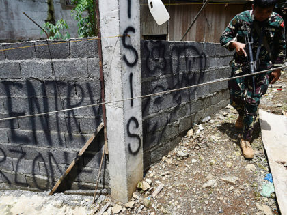 An army trooper walks past graffiti on a concrete fence near the frontline in Marawi on the southern island of Mindanao on June 22, 2017, as fighting between government troops and Islamist militants entered its fourth week. The fighting began on May 23 when hundreds of militants rampaged through Marawi, …