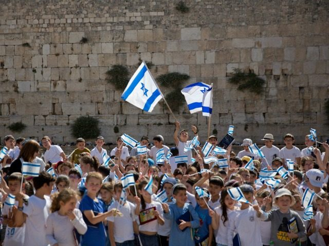 School children wave Israeli flags at the Western Wall, the holiest place where Jews can pray, in Jerusalem's Old City, during Jerusalem Day celebrations, Wednesday, May 24, 2017. On Wednesday Israelis commemorated the capture of the city's eastern sector in the 1967 Mideast war. (AP Photo/Ariel Schalit)