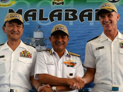 Japanese Rear Admiral Hiroshi Yamamura (L), US Rear Admiral William Byrne (R) and HCS Bisht, vice admiral of the Indian Navy, pose for photographers during the inauguration of joint naval exercises with the United States and India in Chennai on July 10, 2017. India began holding naval exercises with the …