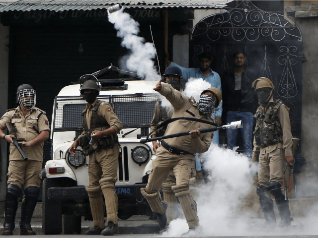 A policeman throws a tear gas shell at Kashmiri protesters demonstrating against Indian rule in Srinagar.Kashmir on Friday. Photograph: Mukhtar Khan/AP