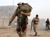 A member of the Libyan National Army (LNA) carries an injured comrade during fighting against jihadists in Qanfudah, on the southern outskirts of Benghazi