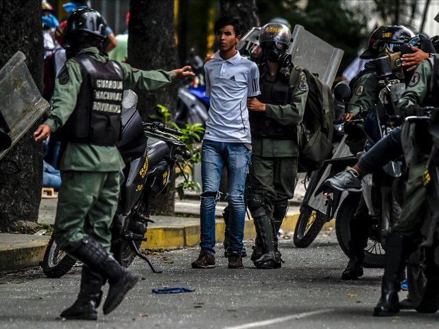 Members of the National Guard arrest an opposition activists during clashes following a march towards the Supreme Court of Justice (TSJ) in an offensive against President Maduro and his call for Constituent Assembly in Caracas on July 22, 2017. The Legislative power, controlled by the opposition, appointed Friday a parallel supreme court in a public session claiming the TSJ judges had been illegally appointed by the parliaments former pro-government majority. / AFP PHOTO / JUAN BARRETO (Photo credit should read JUAN BARRETO/AFP/Getty Images)