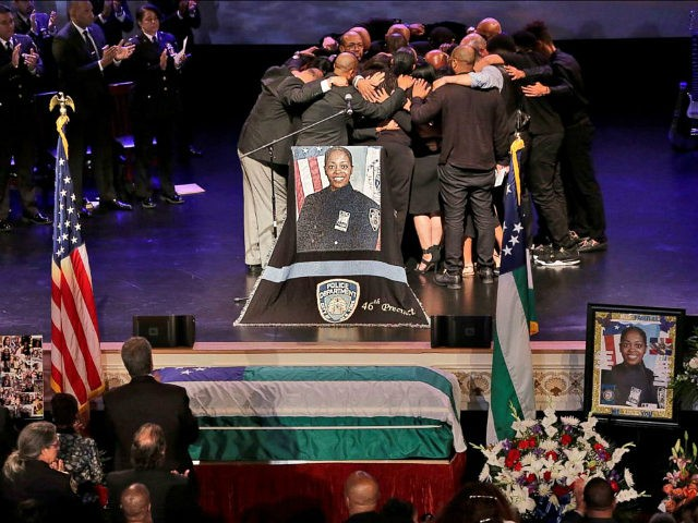 The family of New York City Police officer Miosotis Familia hug during her funeral at the World Changers Church, in The Bronx borough of New York, Tuesday, July 11, 2017. The slain officer, a mother of three children including 12-year-old twins, was writing in her memo book at the end …