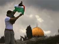 JERUSALEM, ISRAEL - FEBRUARY 16: A Palestinian waves a Palestinian flag as the Dome of the Rock is seen in the Background during clashes outside the Old City on February 16, 2007 in the Eastern district of Jerusalem. Islamic Prayers passed peacefully after about 3,000 police were deployed around the …
