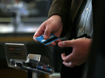 FILE - In this Sep. 3, 2015, file photo, a man pays with a credit card in a Walmart Ekono supermarket in Santiago, Chile. Many retirees avoid credit usage, with unexpected consequences. Keeping active credit accounts can help ensure it's available if you need it. (AP Photo/Luis Hidalgo, File)