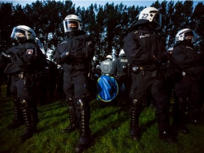 HAMBURG, GERMANY - JULY 02: Riot police surround anti-G20 protesters and the sleeping tents the protesters had erected at a protest camp at Entenwerder Park on July 2, 2017 in Hamburg, Germany. While a local court ruled that the protesters are allowed to gather at the park and install tents, …
