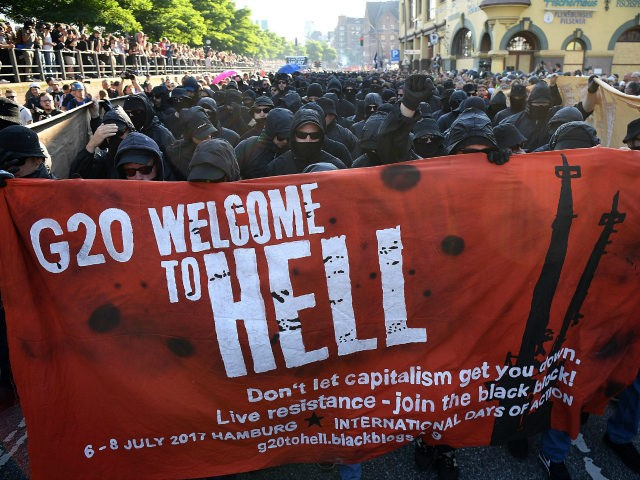 HAMBURG, GERMANY - JULY 06: Protesters dressed in all black hold up a banner as they take part in the 'Welcome to Hell' protest march on July 6, 2017 in Hamburg, Germany. Leaders of the G20 group of nations are arriving in Hamburg today for the July 7-8 economic summit …