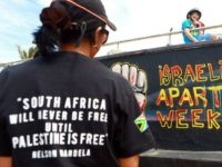 Palestinian activists stand infront of a graffiti as they participate in a protest against Israel at the north beach in Durban on March 10, 2013 ahead of the Israeli Apartheid Week (IAW) from March 11 to 17, 2013 in South Africa. The annual international series of events includes rallies, lectures, …