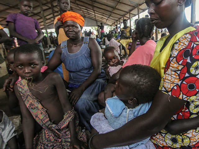 PALABEK SETTLEMENT CAMP, NORTH UGANDA - MAY 2017: South Sudanese refugees Jessica and her niece Lillian wait with others at the Palabek refugee camp reception to be allocated their plot of land in Palabek Settlement camp, North Uganda, May 2017. Unaccompanied children are fleeing violent attacks in South Sudan, travelling …