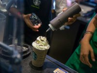 An employee pours syrup over whipped cream while preparing a coffee drink at a Starbucks Corp. coffee shop in Phnom Penh, Cambodia on Monday, Oct. 24, 2016. The Seattle-based coffee chain is expanding in Cambodia to tap the nation's rapid GDP growth. The share of the company's Asian revenue has …