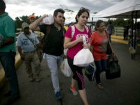 Venezuelans carrying their purchases return to their country through the Simon Bolivar bridge in Cucuta, Colombia, Sunday, July 17, 2016. Tens of thousands of Venezuelans crossed the border into Colombia on Sunday to hunt for food and medicine that are in short supply at home. It's the second weekend in a row that Venezuela's government has opened the long-closed border connecting Venezuela to Colombia. (AP Photo/Ariana Cubillos)