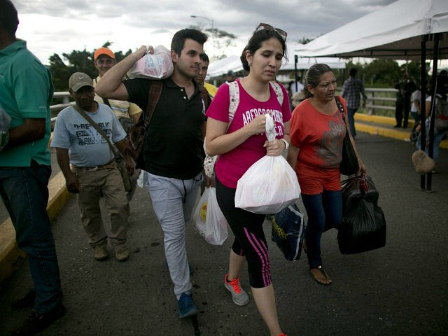 Venezuelans carrying their purchases return to their country through the Simon Bolivar bridge in Cucuta, Colombia, Sunday, July 17, 2016. Tens of thousands of Venezuelans crossed the border into Colombia on Sunday to hunt for food and medicine that are in short supply at home. It's the second weekend in …