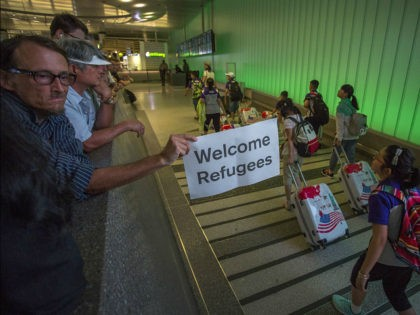 LOS ANGELES, CA - JUNE 29: John Wider carries a welcome sign near arriving international travelers on the first day of the the partial reinstatement of the Trump travel ban, temporarily barring travelers from six Muslim-majority nations from entering the U.S., at Los Angeles International Airport (LAX) on June 29, …