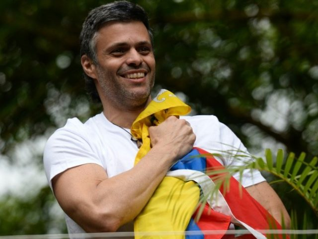 Venezuelan opposition leader Leopoldo Lopez holds a Venezuelan national flag against his chest, as he greets supporters gathering outside his house in Caracas after he was released from prison on July 8, 2017