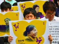 "South Korean protesters hold placards showing portraits of former ""comfort women"". The plight of the so-called ""comfort women"" who were forced into sexual slavery for Japanese troops during World War II is an emotional issue that has marred ties"
