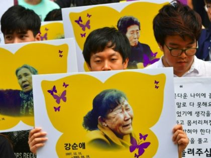 """South Korean protesters hold placards showing portraits of former """"comfort women"""". The plight of the so-called """"comfort women"""" who were forced into sexual slavery for Japanese troops during World War II is an emotional issue that has marred ties"""