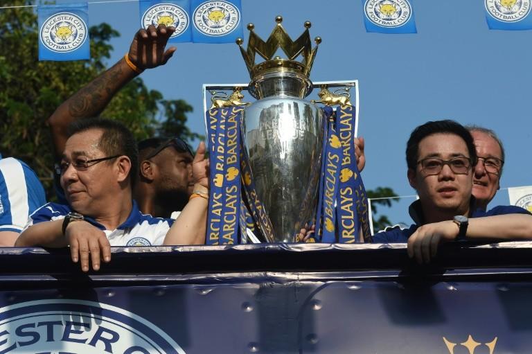 "Leicester City owner Vichai Srivaddhanaprabha (L) and his son and vice-chairman Aiyawatt ""Top"" Srivaddhanaprabha flank the Premier League trophy the team won last season"