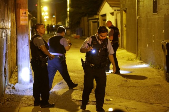 Chicago police search for evidence after a shooting in a Chicago alley this month, part of a surge in gun violence plaguing the US city