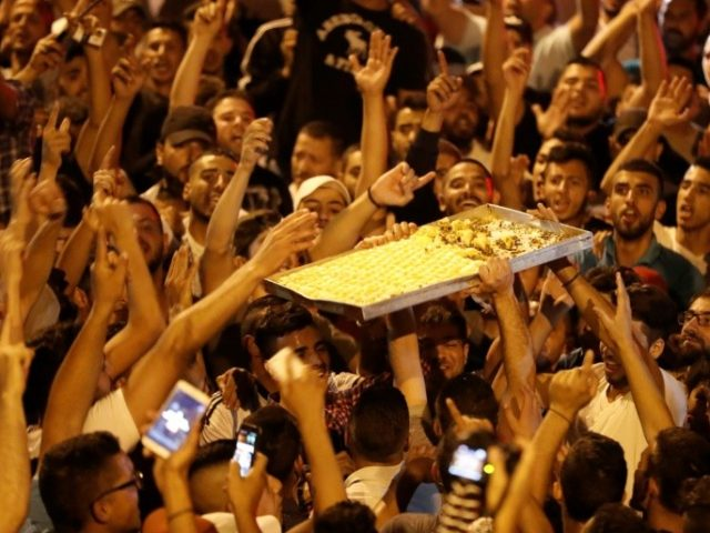 Palestinians celebrate by giving away sweets outside Jerusalem's Al-Aqsa mosque compound on July 27, 2017, after Israeli police removed the last new security barriers from the entrances