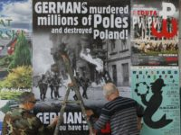 In this Aug. 24, 2017 photo a workers puts up a poster in Warsaw, Poland, calling on Germany to pay reparations for World War II to Poland. Poland's government is calling on Germany to pay it reparations for World War II, when more than five years of brutal Nazi occupation …