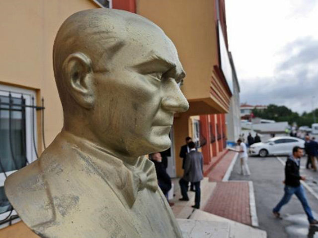 People walk by a bust of Turkish Republic founder Mustafa Kemal Ataturk, at the school that will be the polling station where Turkey's President Recep Tayyip Erdogan will vote later in the day, in Istanbul, Turkey, Sunday, June 7, 2015. Turkey is holding Sunday a general election and approximately 56 …