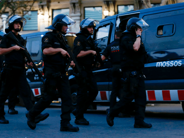 Spanish policemen walk in a cordoned off area after a van ploughed into the crowd, killing 13 persons and injuring over 80 on the Rambla in Barcelona on August 17, 2017.
