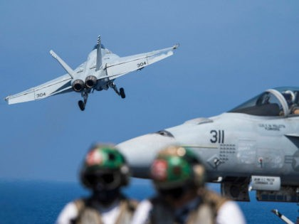 """This US Navy handout photo shows an F/A-18E Super Hornet attached to the """"Tomcatters"""" of Strike Fighter Squadron (VFA) 31 as it launches from the flight deck of the Nimitz-class aircraft carrier USS George H.W. Bush (CVN 77) to conduct flight operations in support of Operation Inherent Resolve June 6, …"""