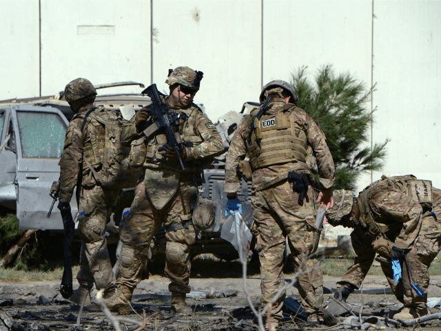 US soldiers inspect the site of a suicide attack in the Afghan capital Kabul on September 16, 2014. A Taliban suicide bomber rammed an explosives-laden car into a NATO convoy close to the US embassy in Kabul on September 16, killing three soldiers and wounding at least 13 Afghan civilians. At the side of the road, US and Polish troops gave first-aid to blood-stained comrades beside the wrecked remains of a military vehicle, but the nationality of the dead soldiers was not confirmed. AFP PHOTO/Wakil Kohsar (Photo credit should read WAKIL KOHSAR/AFP/Getty Images)