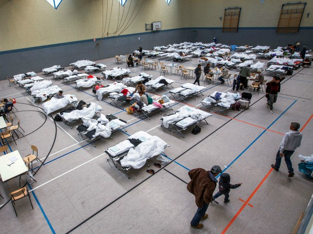 Migrants walk next to camp beds in a makeshift refugee shelter near a first registration center for migrants in a gym in Stern-Buchholz, northern Germany, on September 7, 2015. German Chancellor Angela Merkel said the record refugee influx to Europe's biggest economy will change the country, which was now seen …