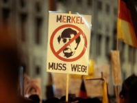 MUNICH, GERMANY - JANUARY 11: Supporters of the right-wing populist group Pegida, holding a placard 'Merkel muss weg' ('Merkel Off') march on January 11, 2016 in Munich, Germany. Pegida and other right-wing activists have been quick to latch on to the New Year's Eve sex attacks in Cologne. Over 100 …